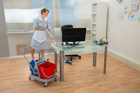 office uniform: Young Happy Female Maid Cleaning Floor In Office