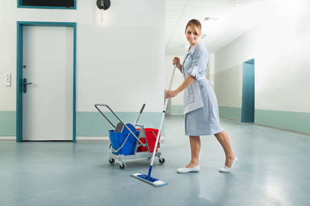 若い幸せな女性用務員廊下などの床清掃