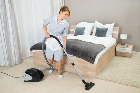 housekeeping: Female Housekeeper Cleaning Rug With Vacuum Cleaner In Hotel Room Stock Photo