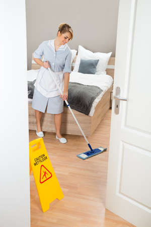 Young Female Maid Cleaning Floor With Mop In Hotel Room photo
