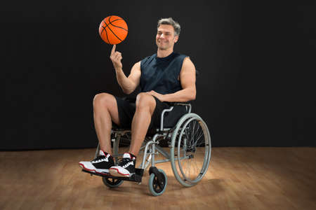 wheelchair: Disabled Basketball Player On Wheelchair Spinning Ball On His Finger Stock Photo