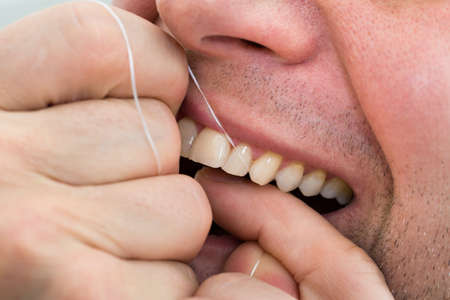 flossing: Close-up Of A Man Flossing His Teeth