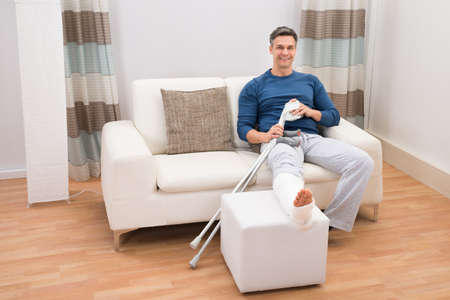 plaster leg cast: Portrait Of A Smiling Man Sitting On Sofa With Crutches At Home