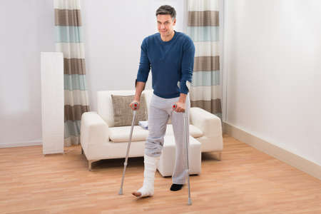 accident patient: Portrait Of A Disabled Man Using Crutches For Walking At Home Stock Photo