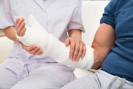 bone fracture: Close-up Of A Female Doctor Holding Fractured Hand Of A Patient Stock Photo