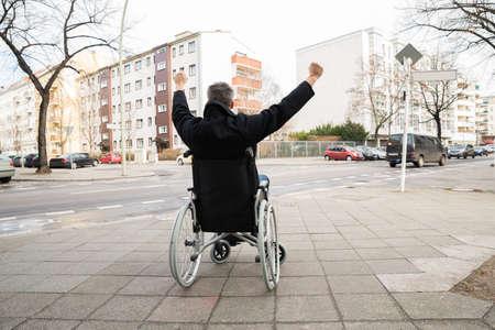silla de ruedas: Vista posterior de un hombre desactivado en silla de ruedas Con Alzar la mano Foto de archivo