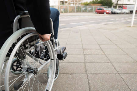 people with disabilities: Close-up Of Disabled Man Sitting On Wheelchair Stock Photo