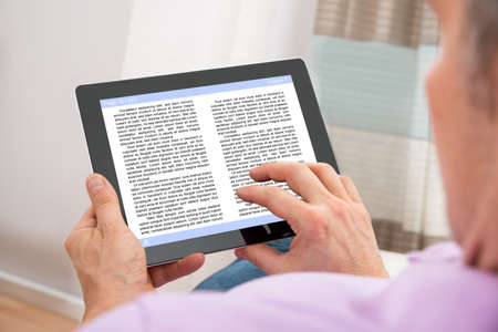 Close-up Of A Man Reading Ebook On Digital Tablet