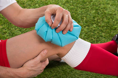 player: Close-up Of A Soccer Player Icing Knee With Ice Pack On Field