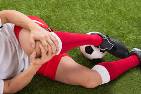 de rodillas: Primer Del Hombre jugador de fútbol que sufre de lesiones de rodilla En Campo Foto de archivo