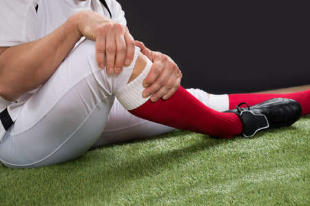 Close-up Of A American Football Player With Injury In Leg On Field photo