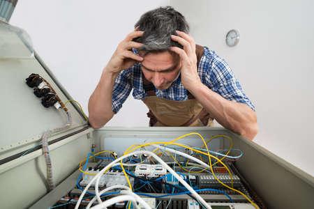 confundido: Retrato de un electricista Confundido Mirando a la caja de fusibles Foto de archivo