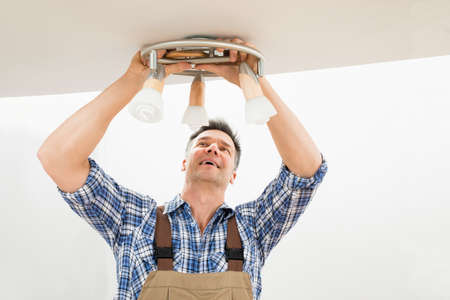 ceiling construction: Portrait Of A Male Electrician Fixing Light On Ceiling
