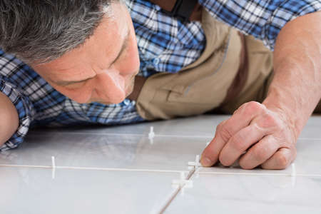 floor covering: Close-up Of A Handyman Lying On Floor Placing Spacers Between Tiles