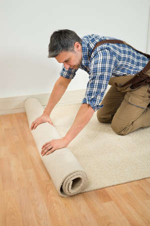 unfold: Male Worker Unrolling Carpet On Floor At Home