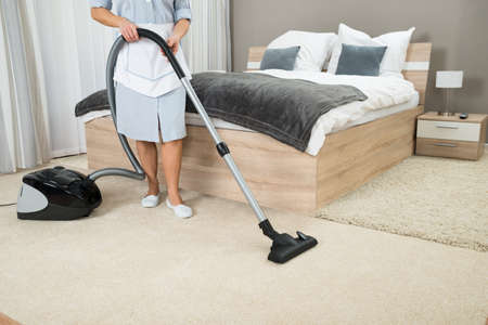 Female Housekeeper Cleaning With Vacuum Cleaner In Hotel Room Stok Fotoğraf
