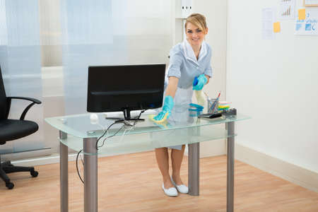 Happy Maid In Uniform Cleaning Glass Desk In Office