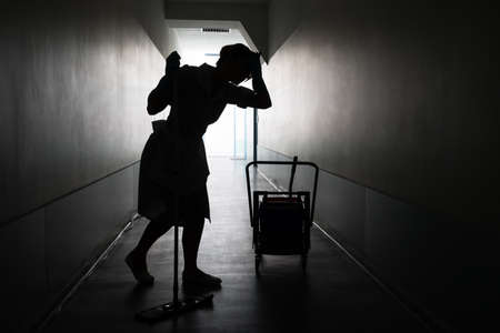 mopped: Silhouette Of Tired Female Maid With Mop In Corridor