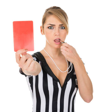 arbiter: Portrait Of Female Referee Holding Red Card While Blowing Whistle