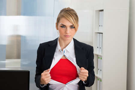 Young Businesswoman Tearing Her Shirt Showing Superhero Suit