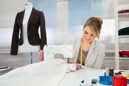 stitching machine: Smiling Fashion Designer Stitching Fabric On Sewing Machine