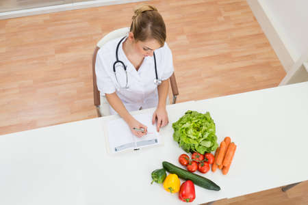 nutritionist: High Angle View Of Female Dietician Writing Prescription With Vegetables On Desk