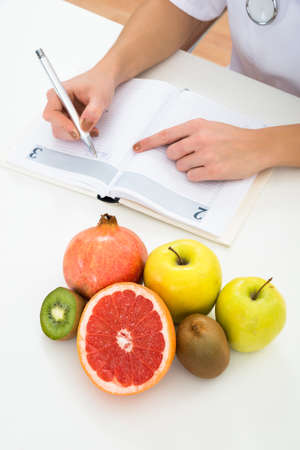 dietician: High Angle View Of Female Dietician Writing Prescription With Fruits On Desk
