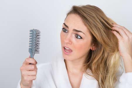 capelli biondi: Preoccupato donna affetta da Hairloss Guardare il pettine Archivio Fotografico