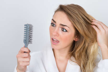 comb hair: Worried Woman Suffering From Hairloss Looking At Comb
