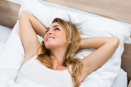 contemplated: High Angle View Of A Young Woman Lying On Bed Daydreaming Stock Photo
