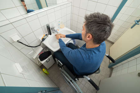 disabled person: High Angle View Of Man On Wheelchair Washing Hands In Bathroom