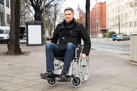 silla de ruedas: Retrato de un hombre sonriente desactivado en silla de ruedas En la Ciudad