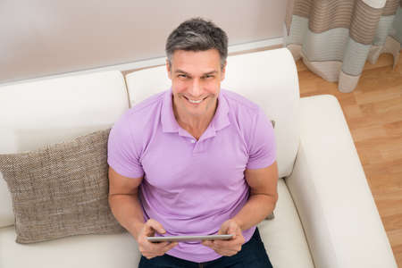 top angle: Happy Man Sitting On Couch Holding Digital Tablet