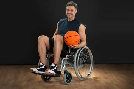 Portrait Of A Disabled Player On Wheelchair Holding Basketball