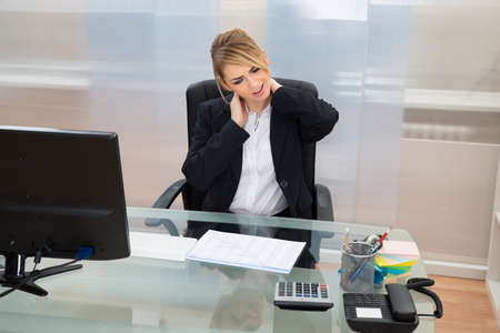Portrait Of Young Businesswoman Suffering From Neckache In Office photo