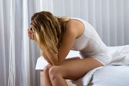 Retrato de joven deprimida Mujer Sentada En La Cama Foto de archivo