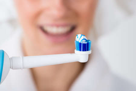 Close-up Of Toothbrush With Toothpaste In Front Of Woman