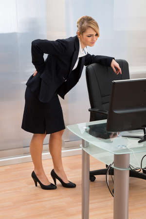 backpain: Young Businesswoman In Office Leaning On Office Chair And Having Backpain