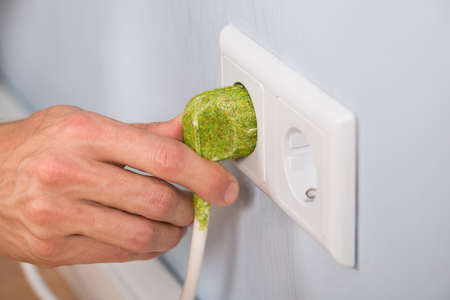 wall socket: Closeup Of Hand Inserting Green Electrical Plug Into A Wall Socket