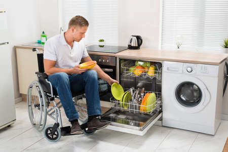 Young Disabled Man Sitting On Wheelchair Working In Kitchen 스톡 콘텐츠