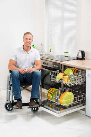 household accident: Young Happy Disabled Man On Wheelchair In Kitchen Stock Photo