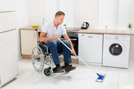 household accident: Disabled Man On Wheelchair Cleaning Floor With Mop In Kitchen Room