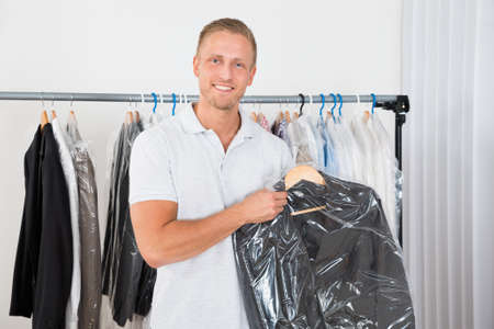 Young Happy Man Holding Coat In Dry Cleaning Store Foto de archivo