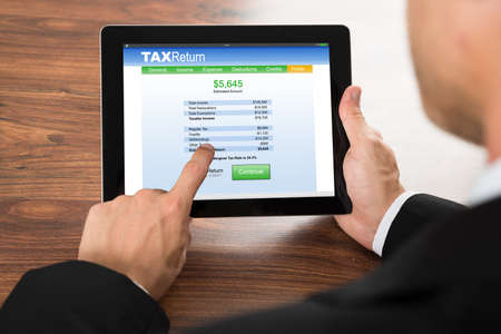 rendement: Close-up van een zakenman invullen belastingaangifte Vorm op digitale tablet Stockfoto