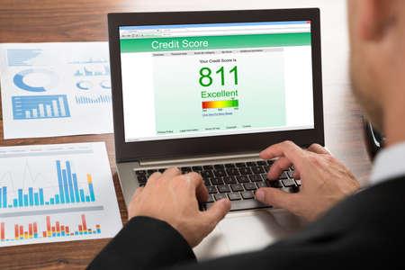 informe: Primer plano de un empresario Comprobación de puntuación de crédito en línea en la computadora portátil Foto de archivo