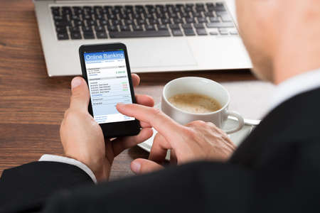 technology transaction: Close-up Of A Businessman Using Online Banking Service On Cellphone While Having Coffee Stock Photo
