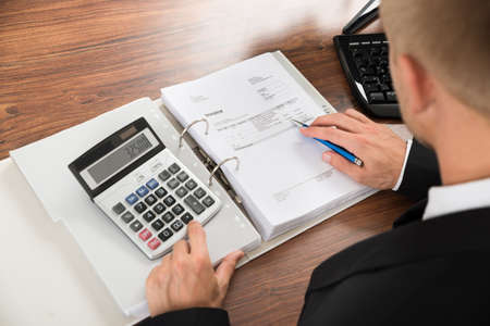 account executive: Close-up Of A Businessman Calculating Invoice Using Calculator At Desk In Office