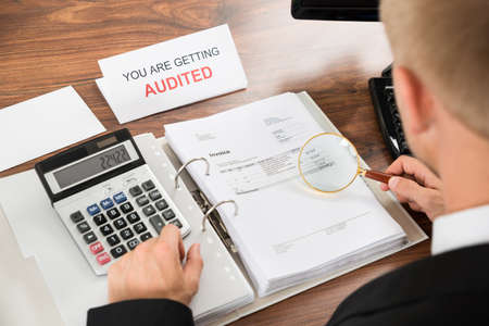 auditor: Close-up Of A Male Auditor Checking Invoice Using Magnifying Glass And Calculator Stock Photo