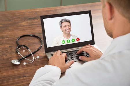 person calling: Primer Del M�dico hablando con el paciente masculino a trav�s de video chat en la computadora port�til en el escritorio