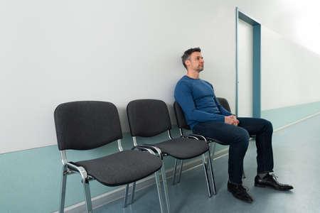 Porträt eines Mitte-erwachsenen Mann sitzt auf Stuhl im Krankenhaus- Standard-Bild